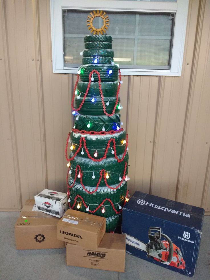 Lawn Mower Tire Christmas Tree. Mower tires painted green, Chainsaw Chain garland, electrical component for star, parts boxes and led lights. Located at Fredonia Outdoor Equipment, Fredonia, KS.