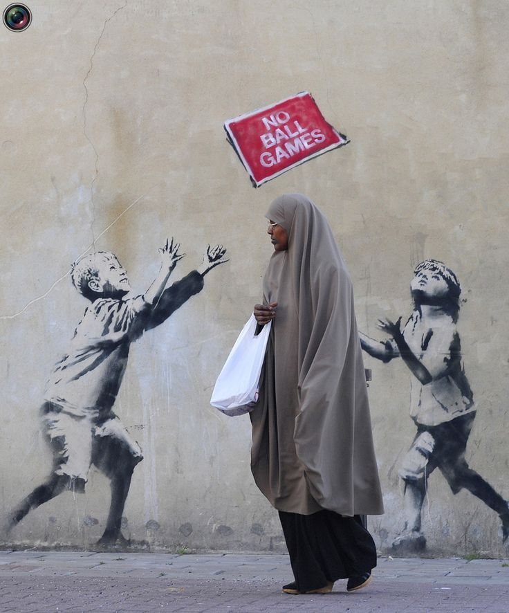 A pedestrian passes graffiti art on a wall in north London, September 24, 2009. British media have attributed the new work to acclaimed British street artist Banksy.