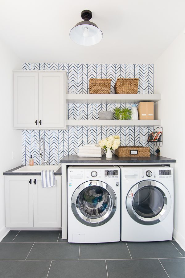 Wallpapered laundry room featuring feather wallpaper from Serena and Lily in Blue. Grey cabinets, open shelving and slate floors.