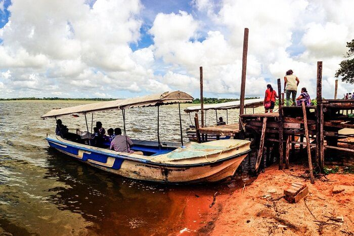A boat docked at the Ousteri Lake as tourists get ready to board the boat for a ride