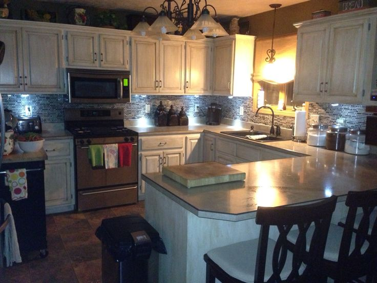Repainted kitchen cabinets from honey oak to antique white and put in glass tile.  Purchased Rustoleum Kitchen Cabinet kit from Home Depot for $69.99...washed, de-glossed, painted, antiqued and put a clear coat on.  The kit has everything you need...you just need the time and patience!