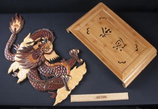 MISCELLANEOUS LOT OF CARVED ASIAN WOOD PIECES INCLUDES A FOUR TONE HEAVILY CARVED AND DECORATED DRAGON WALL PLAQUE DATED 1968 AND MEASURING 24 INCHES. ALSO INCLUDED IN THE LOT IS A CARVED WOODEN TV TRAY OR WRITING TABLE WITH SLIDING STORAGE TRAY UNDERNEATH. MEASURES 20X11 INCHES.