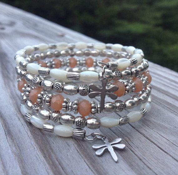 This 5 coil bracelet is made with stainless steel memory wire - will adjust to the size of your wrist and no chance of breaking. This will ensure you will have this bracelet for a long time. Materials include memory wire, Tibetan silver spacers with 3X6mm genuine mother of pearl beads, and 6mm peachy/orange colored micro faceted glass beads. Finished off with an adorable dragonfly charm on each end. The bracelet is on the light to medium side in weight.