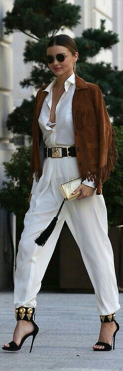 White jumpsuit, brown suede jacket with fringe, spiked heels