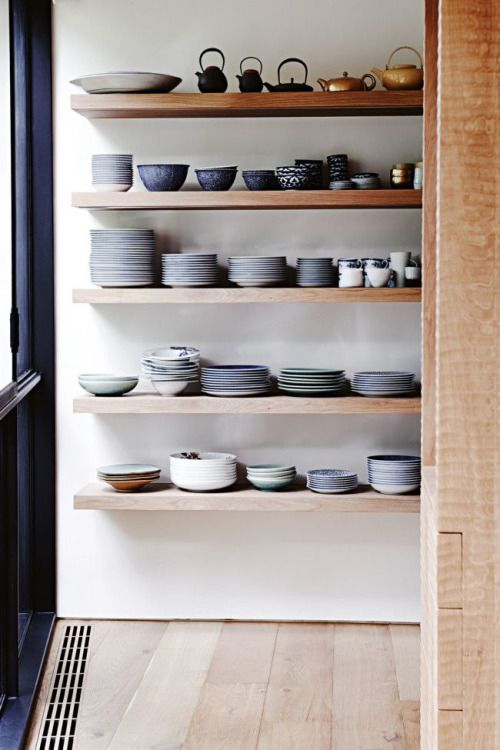 stacked dishes on open shelving