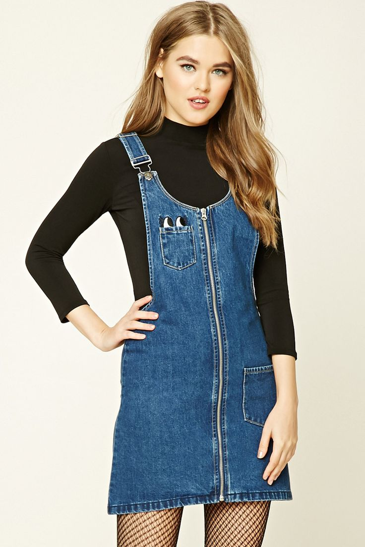 A denim overall dress featuring embroidered eyes, a four-pocket construction, zipper front, and adjustable straps with slide-lock closure.