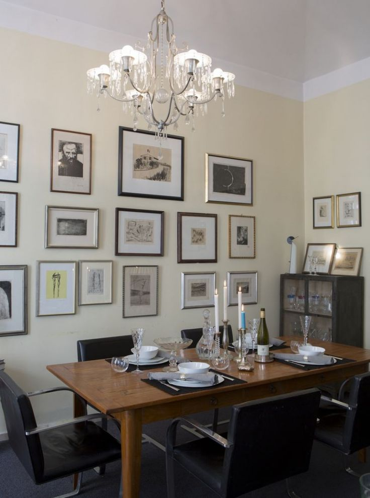 Dining room features Mies Van Der Rohe Brno chairs and a collection of pictures on the wall.