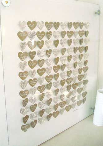 3D Heart Art Guestbook Alternative:  Guests write their messages of love on paper hearts which are then arranged in a shadowbox or a frame as in the photo. This can make a great focal centerpiece for your living room.