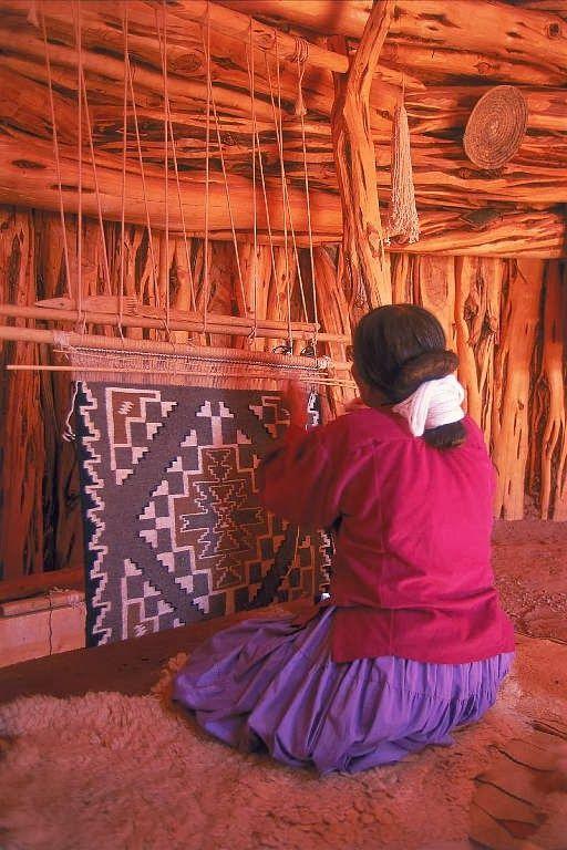 Navajo woman weaving a rug in her hogan