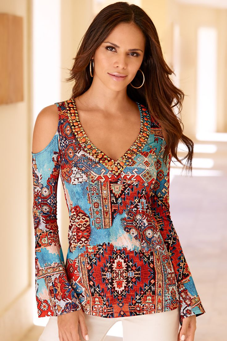 Our wear-now scarf print tunic top inspires wanderlust with its colorful desert hues. Our knit top is detailed with sexy cold-shoulder cutouts, embellished v neckline and flare sleeves.