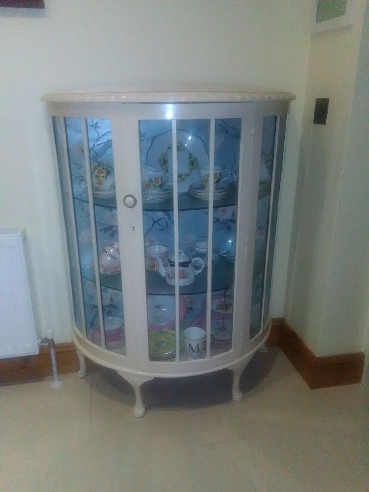 China cabinet painted in antique white and lined with wallpaper