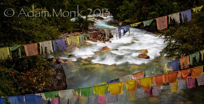 Prayer flags over a wild river in Bhutan.  Photographic tour of Bhutan with Adam Monk 2013