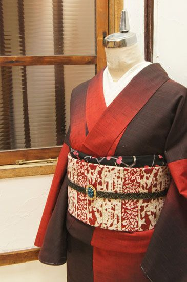 赤とチャコールブラックの暈し織りも美しくデザインされた段違い縞がモダンなウールの単着物です。