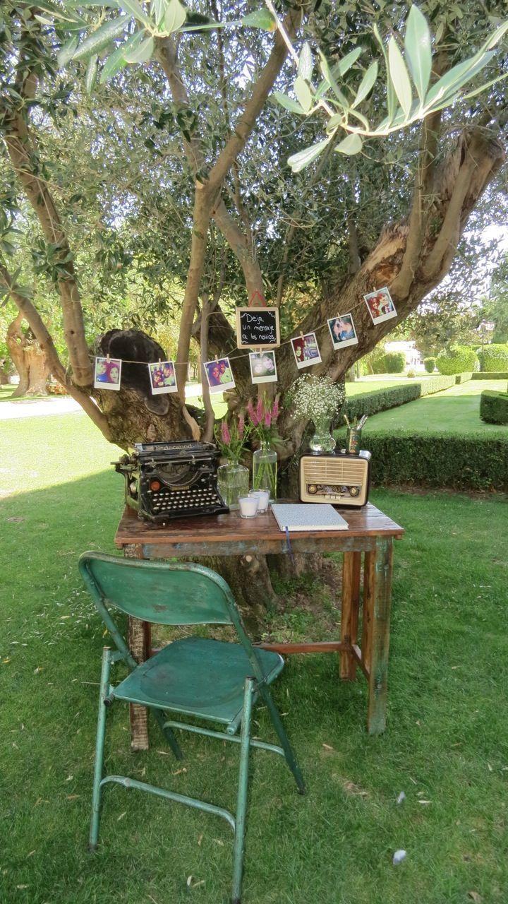 Mesa de firmas frente a olivo con elementos antiguos y banner de fotos. En colaboración con Sara de Wedandbazaar.