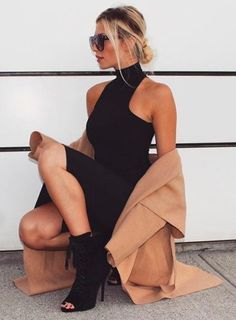 High neck black dress + camel coat.
