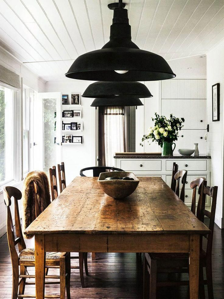 Antique Timber Dining Table And Chairs Beneath A Trio Of Black