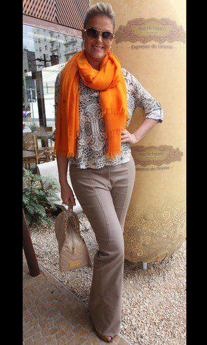 A apresentadora Ana Hickman usou uma calça flare social de cor nude com uma blusa branca estampada em tons de verde, mais solta. Os saltos são ótimas dicas para usar com esse estilo de calça e o cachecol laranja deu uma cor ao look, que foi finalizado com a bolsa de correntes, também nude.