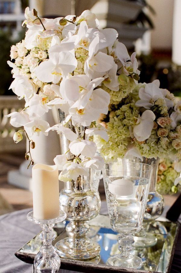 Gorgeous mercury glass vases with white flower bouquets on