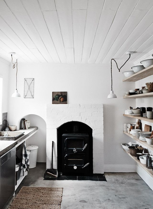 White kitchen with black fireplace and wooden shelves at the dreamy The Estate Trentham. Photo Lisa Cohen.