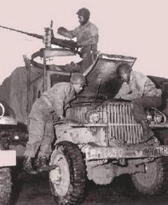 U.S. Army Transportation Museum.Members of the Red Ball Express repair a truck while a crewman at a machine gun keeps an eye out for enemy a...