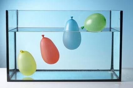 Experimente für Kinder: Alles, was leichter ist als Wasser, schwimmt. Luft ist leichter als Wasser. Deshalb schwimmen die Wasserbomben mit viel Luft oben. Die Wasserbombe, die nur mit Wasser gefüllt ist, versinkt.