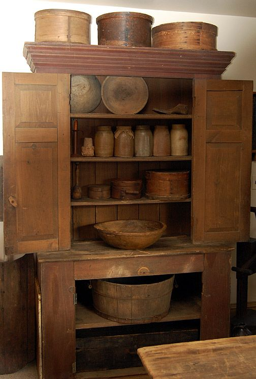 Step back cupboard with storage jars and wooden bowls.                          ****