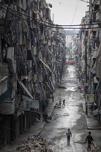 For the last month, photographer Narciso Contreras has been showing the destruction in Aleppo, Syria. Here, people walk past damaged homes during heavy fighting between Free Syrian Army fighters and government forces