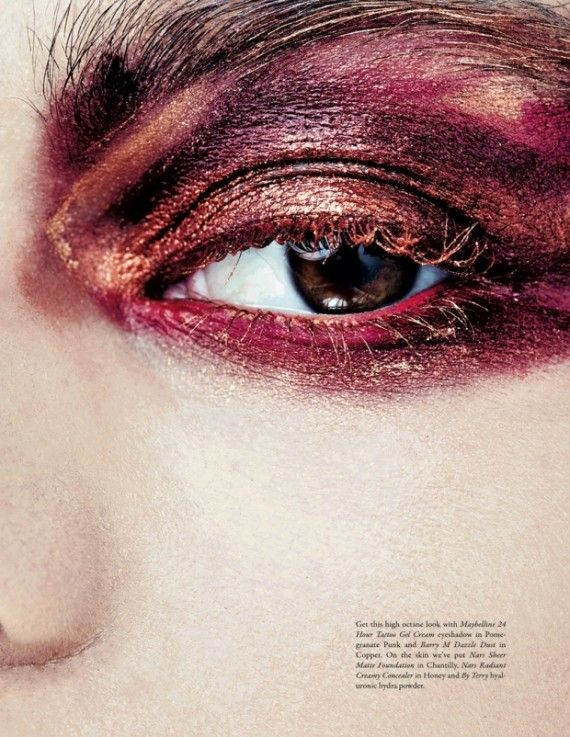 Bold eyeshadow covering top and bottom lid with lashes. Colours; red with hints of gold