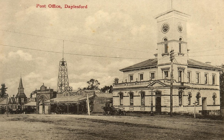 The Daylesford Post Office with a blacksmith/ironmonger next door and the Fire Station nearby. The Daylesford primary School is also in the image and a very old car.   The Fire station is now home to the Daylesford Visitors Centre.