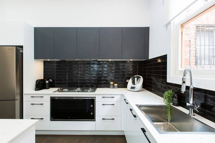 Black and white kitchen love! The black overhead kitchen cabinetry is incredible and softened with white lower cabinets (love those sleek black handles). That black straight stack subway tile splashback is so cool! See loads more pics from this kitchen on the blog >>