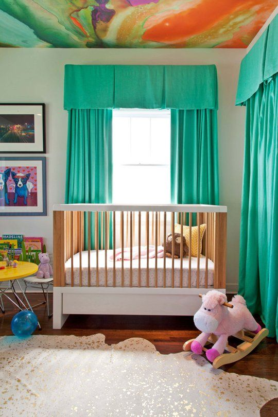 """Talk about """"wow factor"""" - a watercolor wallpaper on the ceiling of this colorful girl's nursery"""