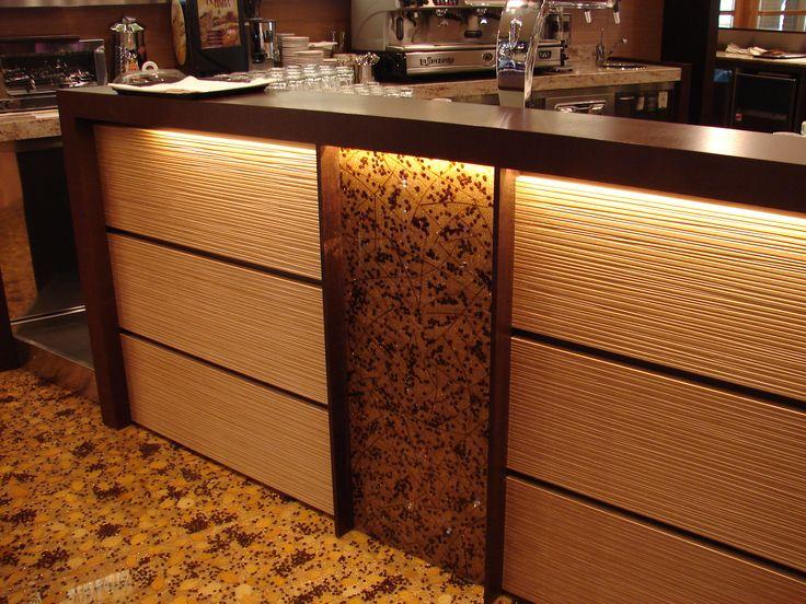 Pannello centrale del bancone bar. Chicchi di caffè su fondo in iuta e foglie immersi in resina trasparente.