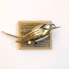 Vogel gemaakt van upcycled gebruiksvoorwerpen en schroot gemonteerd op teruggewonnen hout.  Hoogte: 3  Breedte: 6,5  Diepte: 3