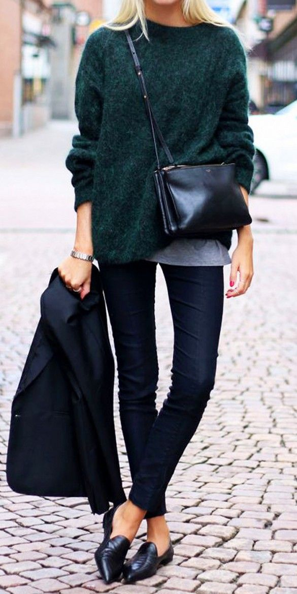 A dark green sweater is worn over a grey shirt, blue jeans, a black crossbody bag, and black pointed toe loafers.