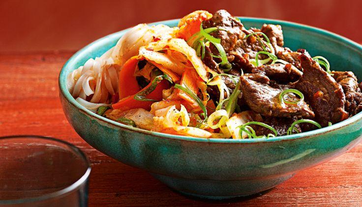Kom in Aziatische sferen met deze rijstnoedels met geroerbakt rundvlees en snelle kimchi. Smaken van gember, vissaus en cayennepeper voeren je ver weg!