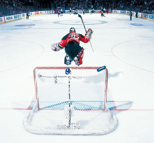 Devils goalie Martin Brodeur jumps in the air to celebrate Jason Arnott's series clinching goal in the second overtime of Game 6 of the 2000 Stanley Cup Final. (David E. Klutho/SI)