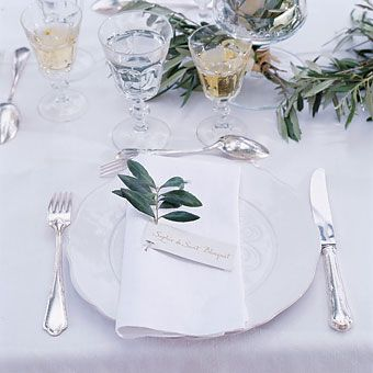 Brides: Fresh Olive Twig Escort Card. The wedding table, decorated with an olive leaf garland studded with white roses. The place settings included place cards anchored with an olive twig.