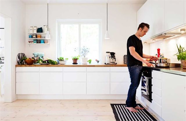 clean white kitchen, with a white pocket string shelf. combination of wood + steel boards
