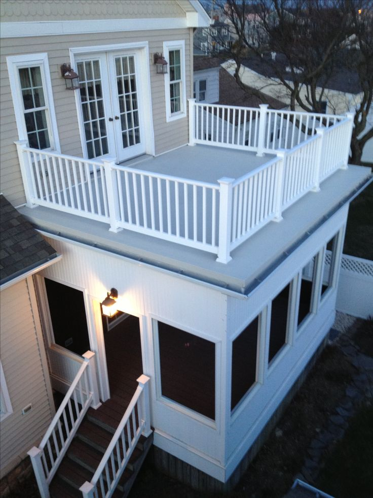 flat roof with railings and a screened in porch wife can