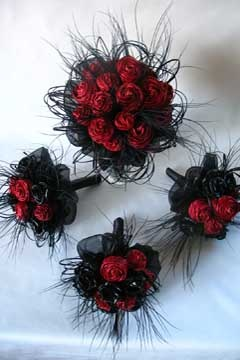 Red flax flowers with black bear grass loops and tumble weed spikes fully bound in black satin.