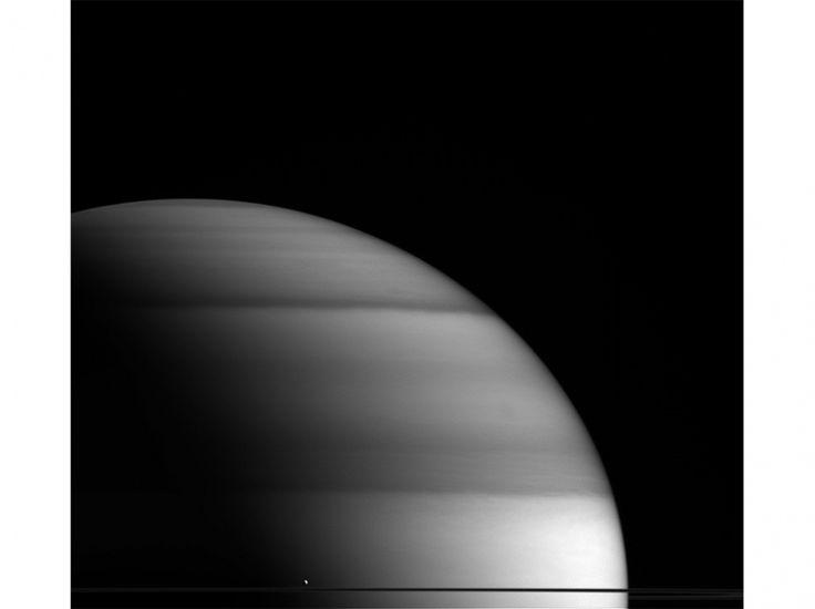 Une des lunes de Saturne, Encelade, 504 kilomètres de diamètre, est un point en bas de l'image.