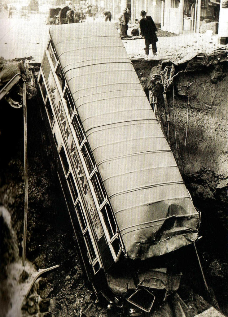 A bus lies in a deep crater in Balham, South London, following night time bombing - 14 October 1940