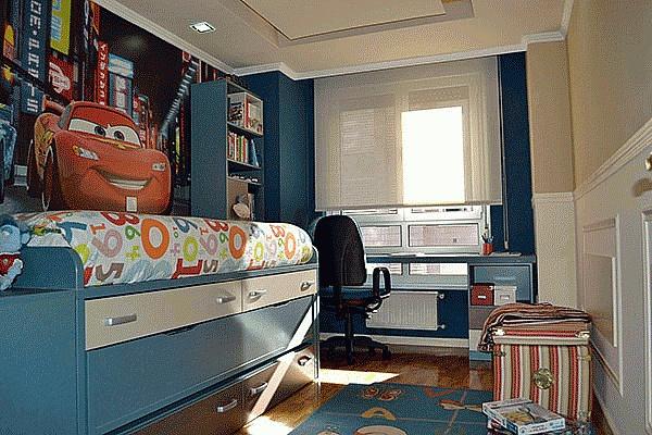 Dormitorio juvenil de dos camas, con cama nido, estanterías y mesa escritorio.