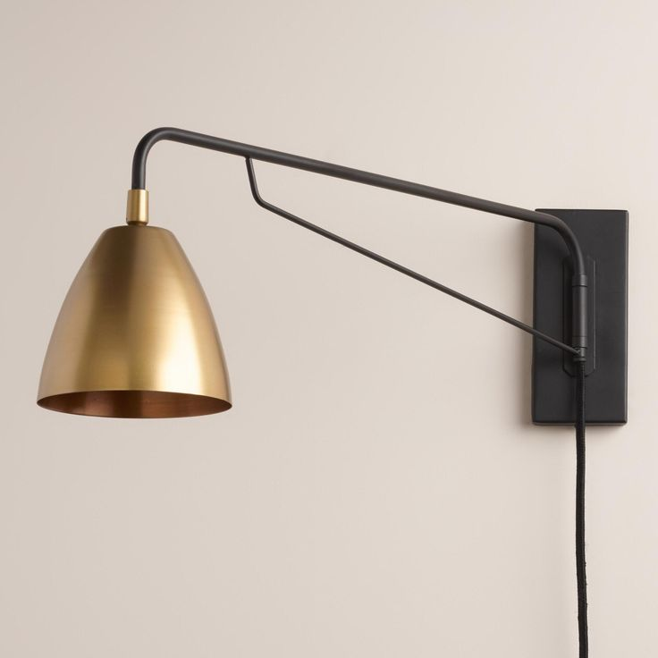 Crafted with a pivoting arm and adjustable antique brass shade inspired by mid-century modern design, our exclusive wall sconce is a custom lighting solution for any dark corner with a plug-in cord for easy installation.