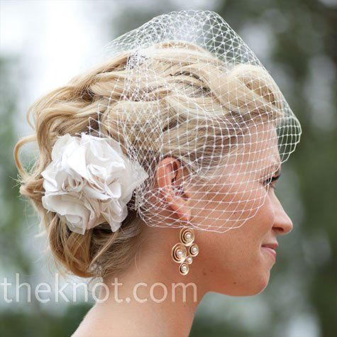 The fabric flower attached to the bride 39s birdcage veil matched her dress