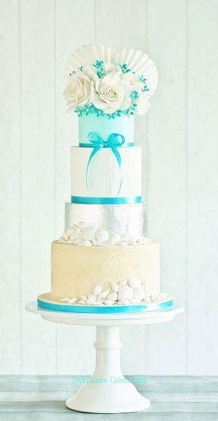 "Strand taart met eetbaar bladzilver, witte rozen, suiker schelpen en eetbaar ""zand"" / Beach themed cake with edible silver leaf, sugar shells and edible ""sand""."