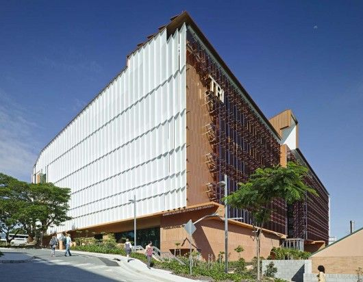 The 344,000-square-foot Translational Research Institute (TRI) embraces Brisbane's subtropical climate through a variety of measures. Rose-tinted engineered glass on the northern facade modulates sunshine in the workspaces. A sun screen of perforated aluminum shades, clipped to the eastern and western sides, provides optimum ultraviolet protection while opening up key views. Image © Christopher Frederick-Jones