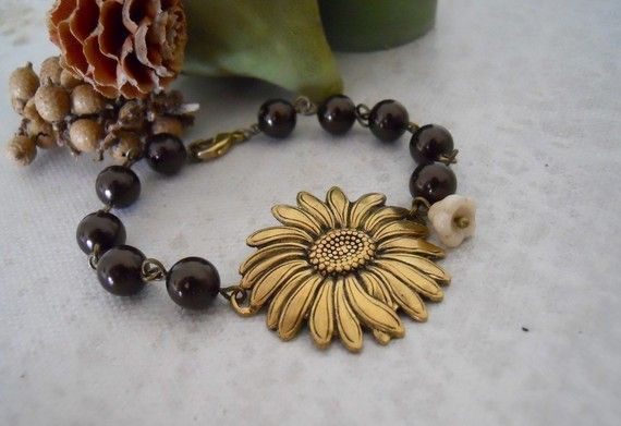 This unique bracelet features a Antique brass sunflower charm adorned by a creamy flower and ten beautiful chocolate color glass pearls.