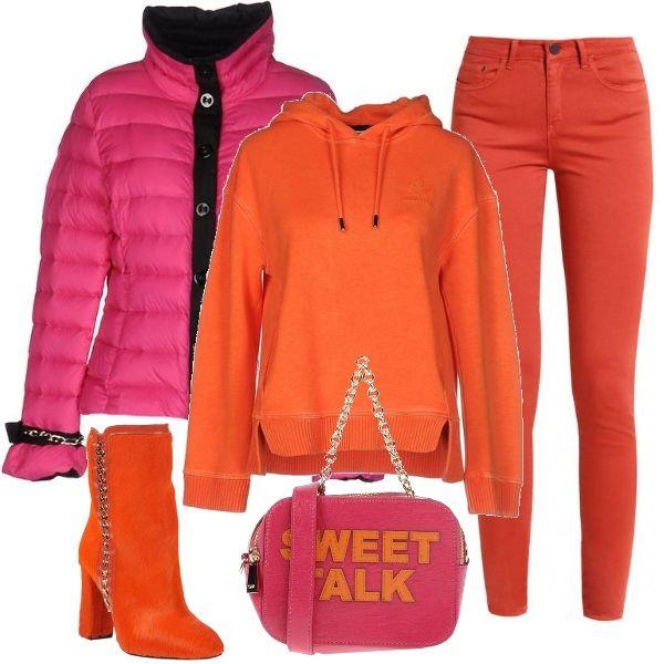 Abbinamento fluo per questo look informale. I jeans skinny e la felpa di cotone arancioni sono indossati con un piumino corto fucsia. Gli stivaletti in pelle di cavallino arancione sono abbinati al piccolo bauletto con tracolla in metallo, porpora e arancio.