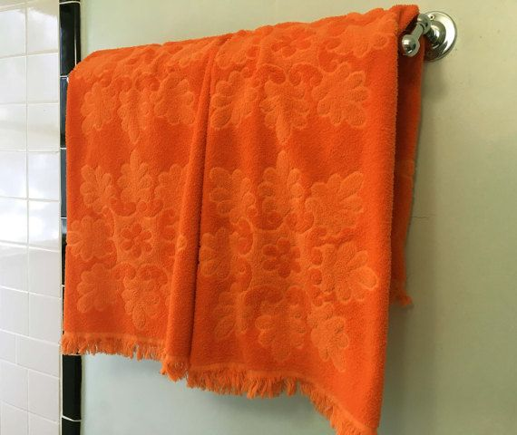 A pair of orange terry cloth bath towels There is a sculpted floral design on one side. On the other side the design is flat terry cloth with the colors reversed. The front is not velour, but regular terry cloth No tags or markings 25 x 39 The color in the 2nd photo is the most accurate. Good vintage condition - they dont look as if they have been used much. They are still fluffy and the colors are bright. There are a some minor pulls in the terry cloth. I will combine shipping when possi...